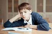stock photo of diligent  - Diligent preschool sitting at desk classroom - JPG