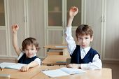 foto of diligent  - Diligent preschools sitting at desk in classroom - JPG