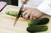 stock photo of cucumber slice  - Chef slicing cucumbers in kitchen on cutting board - JPG