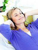 Relaxed Caucasian Woman Listening To Music With Headphones Lying On A Sofa