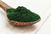 stock photo of algae  - Closeup of an organic spirulina algae powder in a wooden spoon on white wooden background - JPG