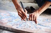 stock photo of carving  - Vietnamese craftsman carving out and painting a floral pattern on a wooden board - JPG