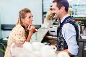 picture of flirt  - Girl in cafe or coffee bar flirting with barista who is busy preparing Cappuccino with professional machine - JPG