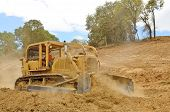 pic of bulldozers  - A large bulldozer spreads dirt and rock for a new fill layer on a commercial construciton road project - JPG