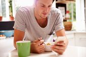 foto of check  - Man Eating Breakfast Whilst Checking Mobile Phone - JPG