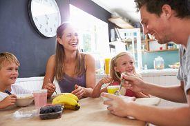 image of breakfast  - Family Eating Breakfast At Kitchen Table - JPG