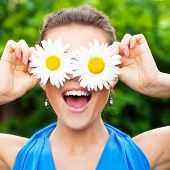 attractive young adult covering her eyes with white chamomile and laugh out loudly