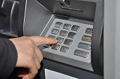 Someone pressing number button on ATM machine
