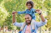 Smiling father holding his son on shoulder and looking at camera. Portrait of happy african dad litt poster