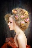 artistic fashion portrait of a beautiful woman with roses in her hair