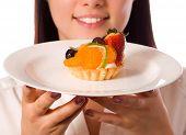 Постер, плакат: молодая женщина с низкокалорийный торт фокус на торт