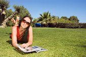 Schöne junge Frau im Park Magazin lesen