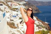 Beautiful young woman on the streets of Oia, Santorini, Greece.