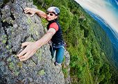 Young white man climbing a steep wall in mountain, rock-climb extreme sport, summer season. Horizont