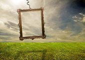 Empty retro frame hanging on poor grassy land. Conceptual.