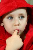 child in red bathrobe licking his finger
