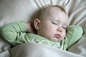 18 months old baby boy sleeping in bed and dreaming
