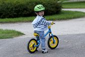 2 years old child learning to ride on his first bike