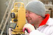 Topógrafo trabajando con Teodolito en un sitio de construcción