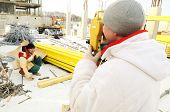 Topógrafo, trabajando con equipos de teodolito en una construcción en invierno