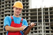 One happy builder worker with clipboard inspecting construction site