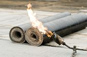 stock photo of overhauling  - roofing felt roll and one torch blowpipes with open flame - JPG