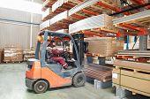 Worker driver of a forklift loader at warehouse loading wood furniture to shelves