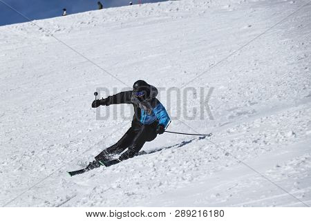 A Male Skier Skiing Downhill