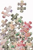 Jigsaw puzzles superimposed with world major currencies scattered on white background
