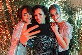 Image of a beautiful young happy women friends posing over glitter wall background take a selfie by  poster