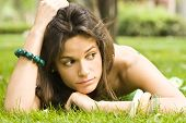 Sad young woman laying on the grass