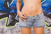 Sensual young woman belly over grafted wall