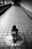 Young woman in white dress on the floor, dark black and white.