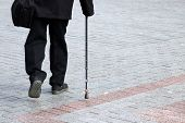 Man Walking With A Cane On The Street, Rear View. Concept Of Limping Person, Disability, Old Age, Bl poster