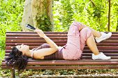 Beautiful woman reading in a park bench.