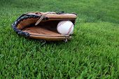 Ball glove and baseball on outfield grass. It's time to play ball.