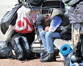 Without Hope - a homeless man bows his head as he sits amongst the only items he owns in a shopping cart.