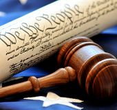 Legal Decision-making. Closeup of gavel with constitution and flag in background.