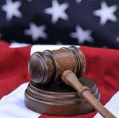 Law of the land - wooden gavel atop a US flag background. Portrayal of the Judicial Branch of govern