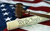 We The People - US Constitution document with wooden judge's gavel atop American flag background.