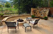 Custom home backyard firepit and waterfall along a golf course. Luxurious relaxing image with patio furniture.