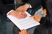 A business woman show the place on the document where the director should sign.