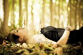 Young beautiful gothic girl laying over the foliage.