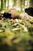 stock photo of gothic girl  - Young beautiful gothic girl laying over the foliage - JPG