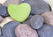 a Green heart of stone between multi colored natural stones