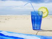 Blue glass with sparkling water and lemon next to a towel on the beach on a summer day