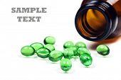 Verdes comprimidos com frasco de comprimido sobre um fundo branco com espaço para texto