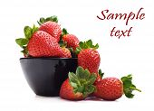 Healthy fresh strawberries and a bowl on a pure white background with space for text