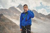 Portrait Of A Professional Guide-mountaineer In A Cap And Sunglasses With An Ice Ax In His Hand Smok poster