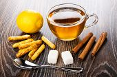 Bread Sticks With Poppy, Lemon, Cup Of Tea, Teaspoon, Sugar Cubes, Cinnamon Sticks On Dark Wooden Ta poster